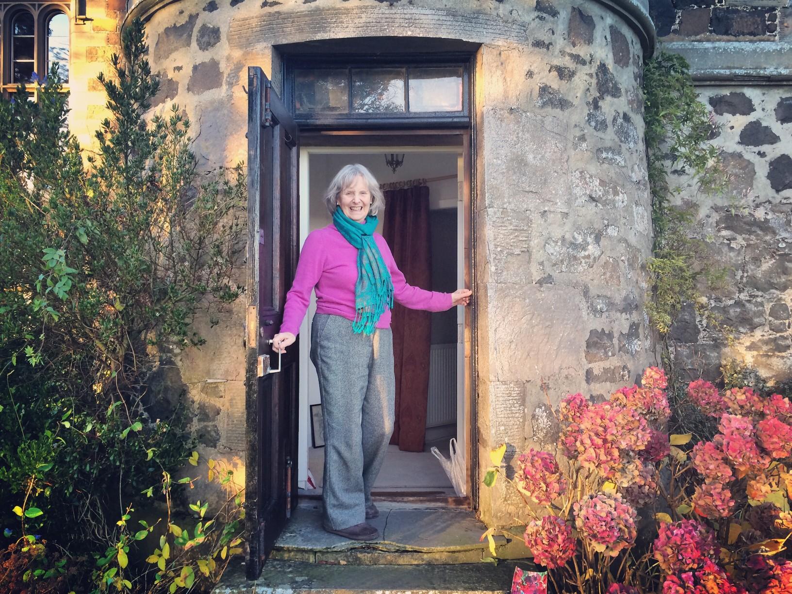 senior-woman-opening-door-to-her-home
