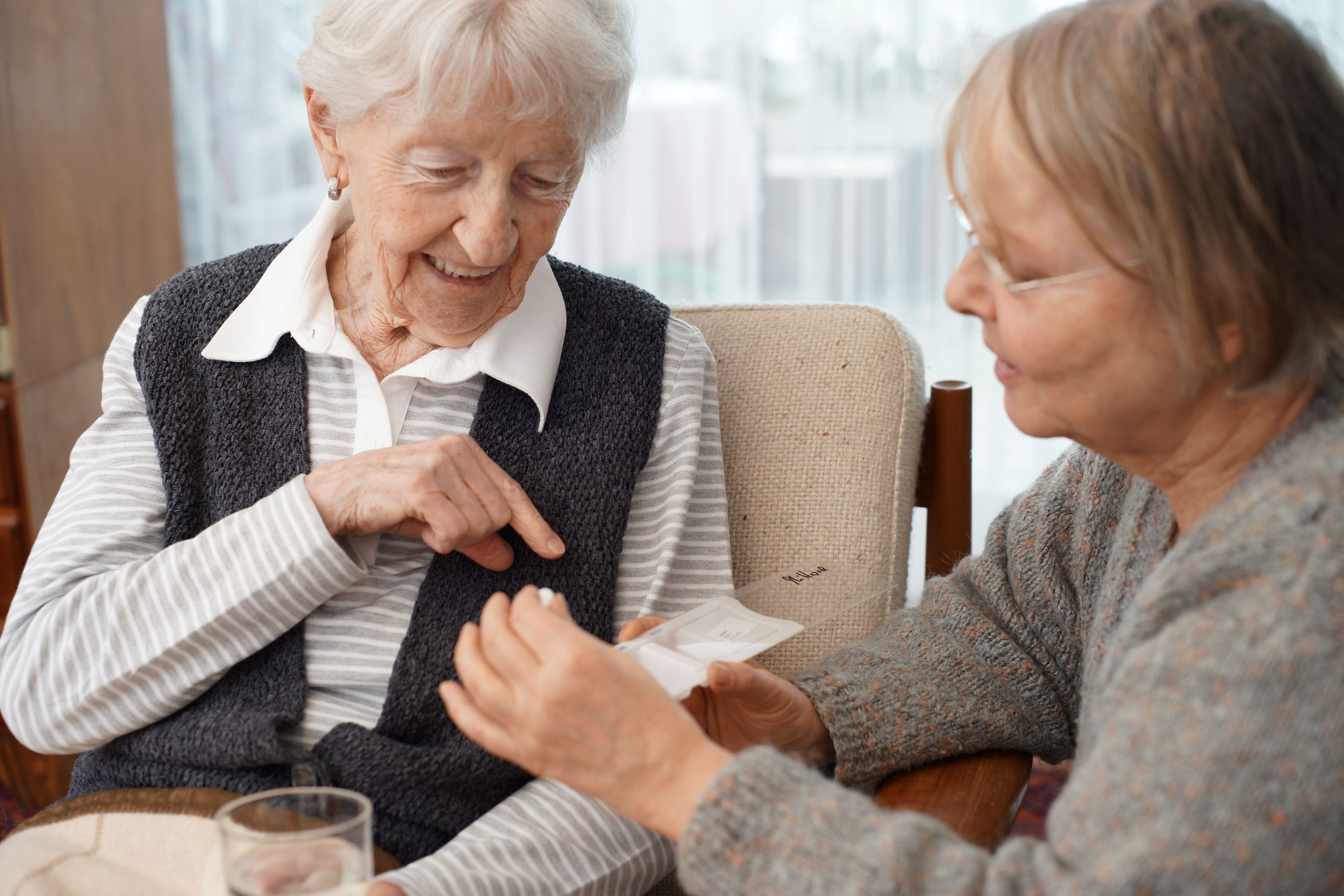 older-woman-sitting-and-pointing-to-medication-with-her-daughter