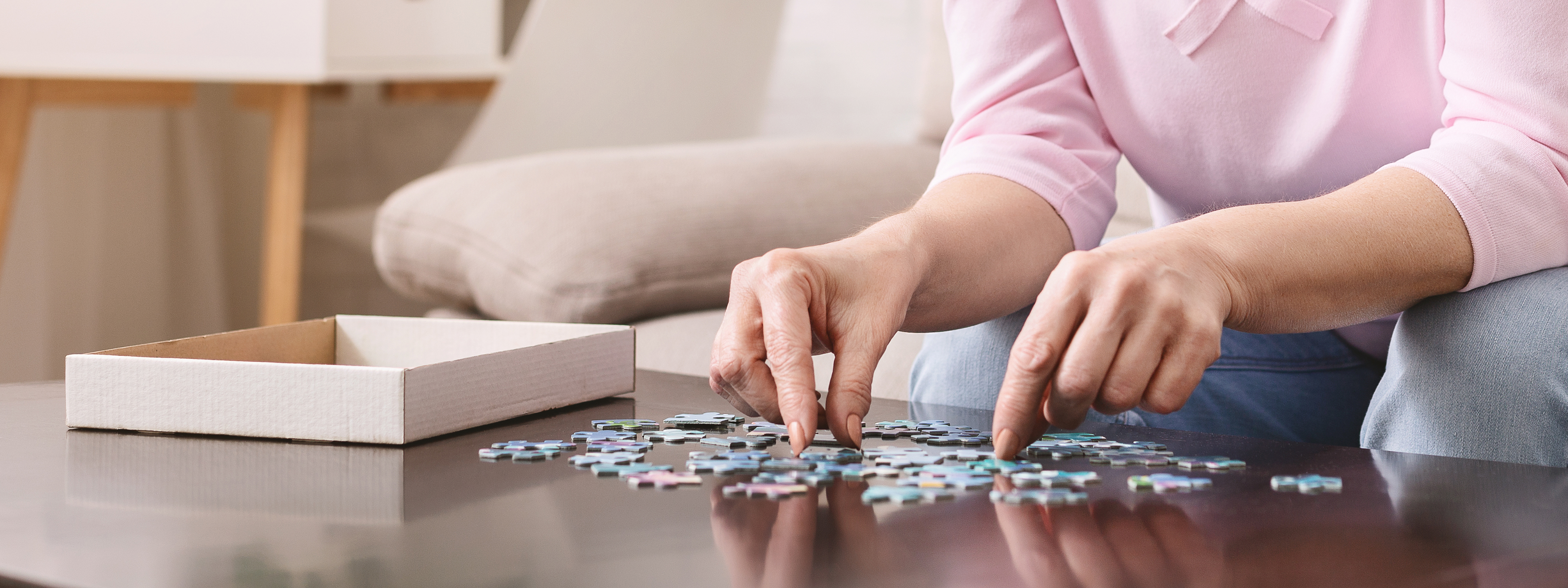 elderly-female-hands-trying-to-connect-pieces-of-puzzle