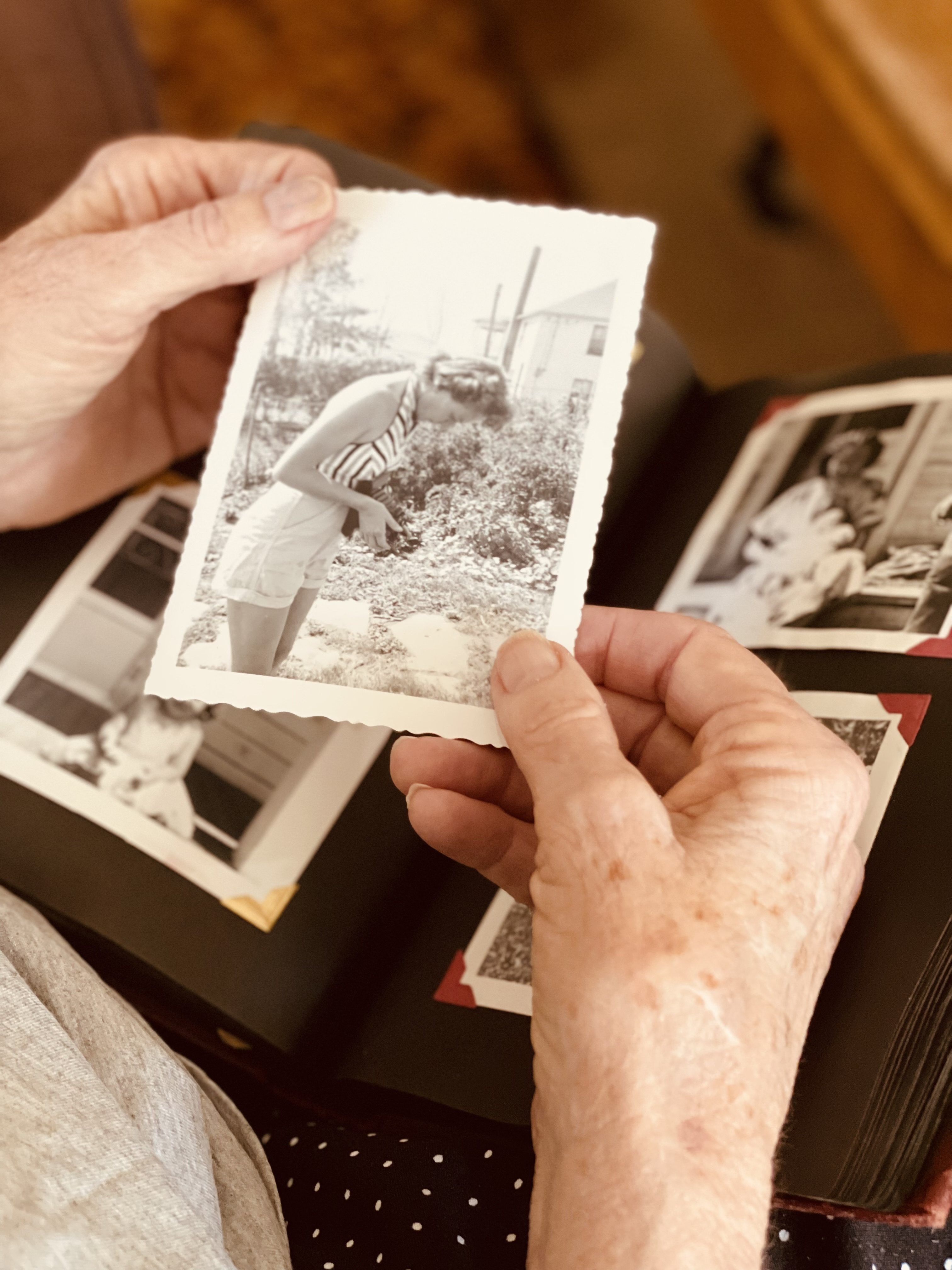 elderly-woman-holding-old-black-and-white-framed-photo-of-her-grandmother-reminiscing-about-family-tree