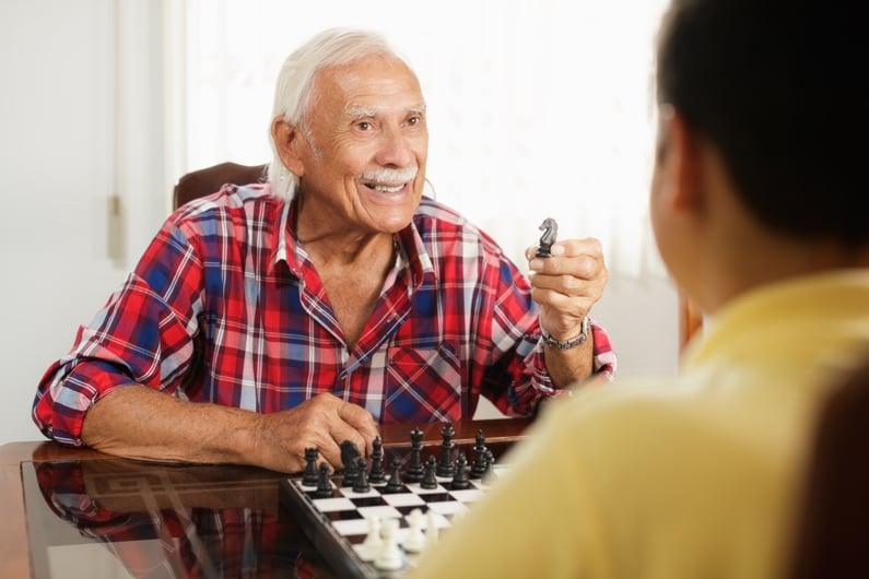 grandpa-playing-chess-board-game-with-grandson-at-PBXQVA9