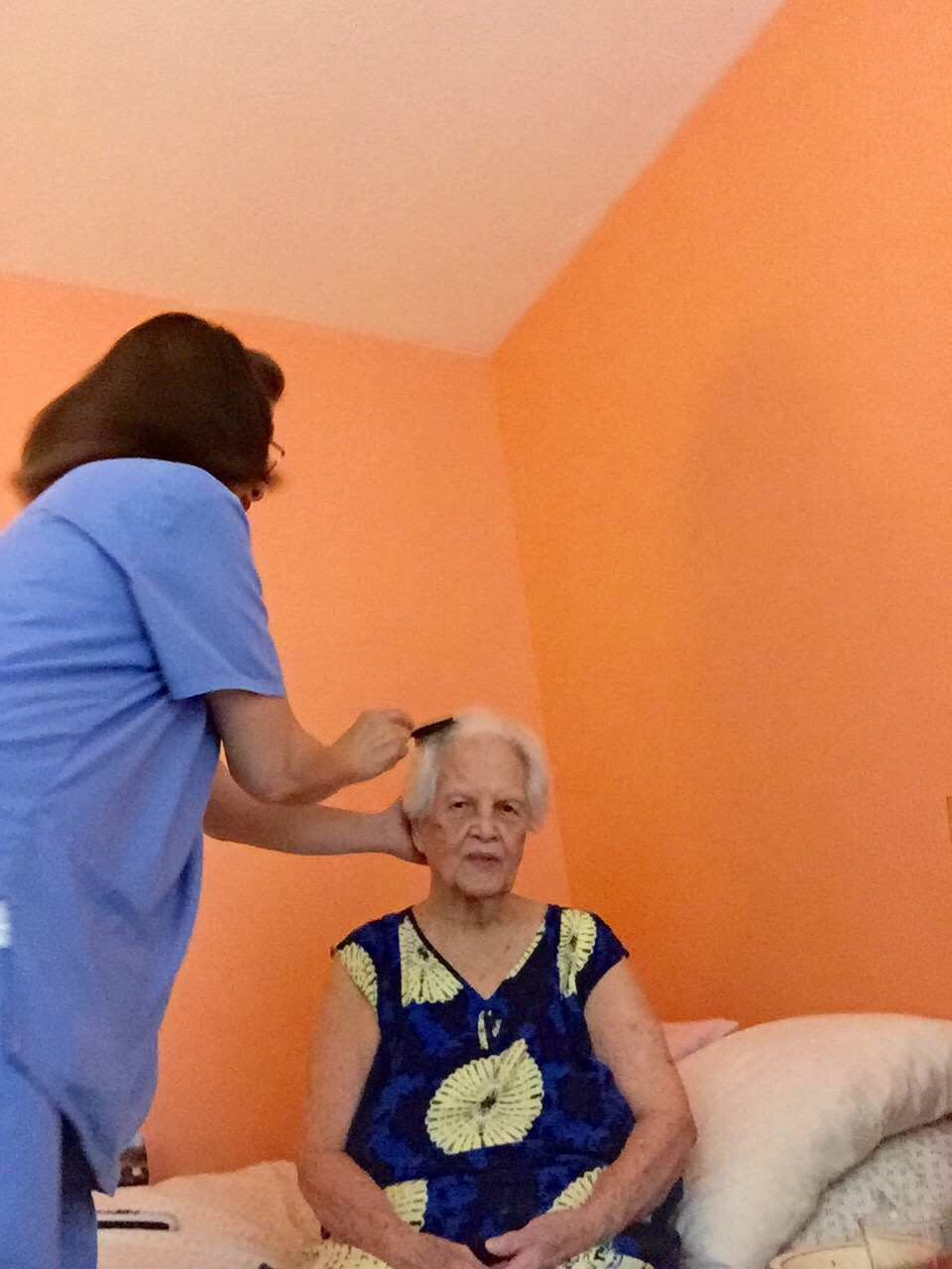 caregiver-brushing-senior-womans-hair