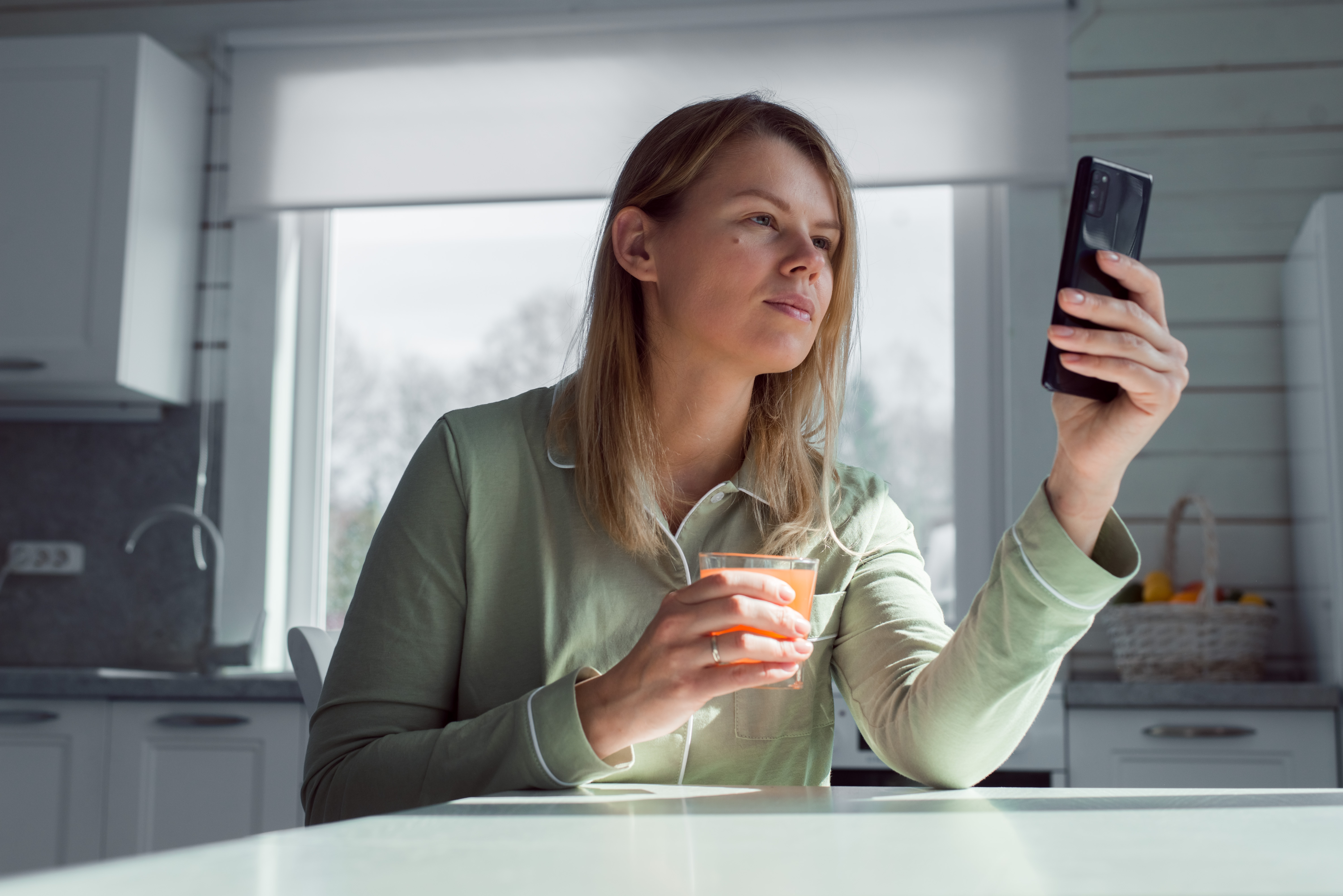 woman-looking-at-her-phone-at-kitchen-counter-in-blouse