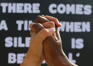 image-of-caucasian-and-african-american-hand-gripped-together-in-foreground-with-black-lives-matter_t20_lL17bg