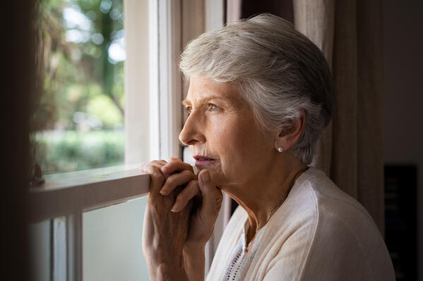lonely-senior-woman-looking-out-window