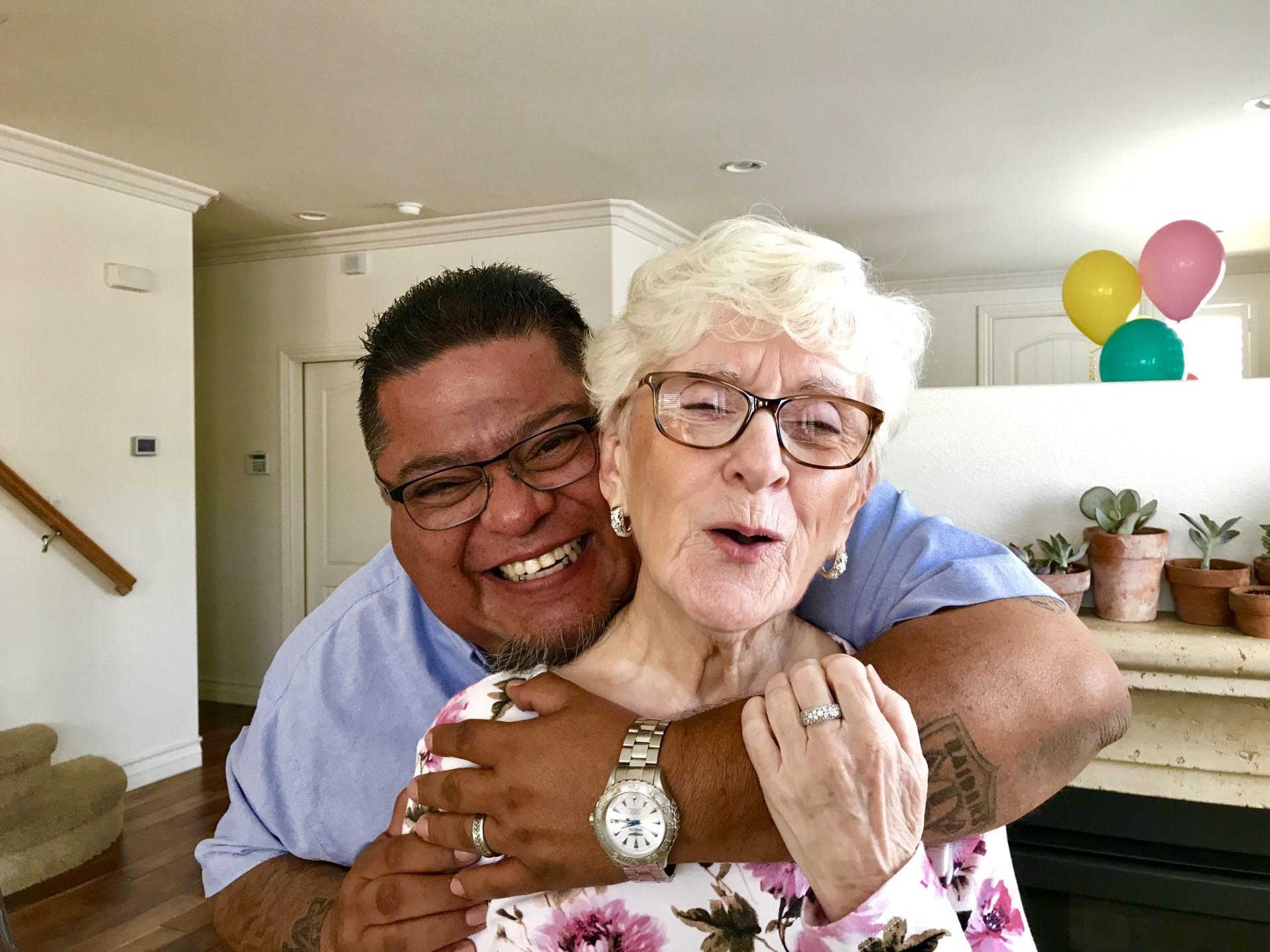 man-hugging-smiling-senior-woman