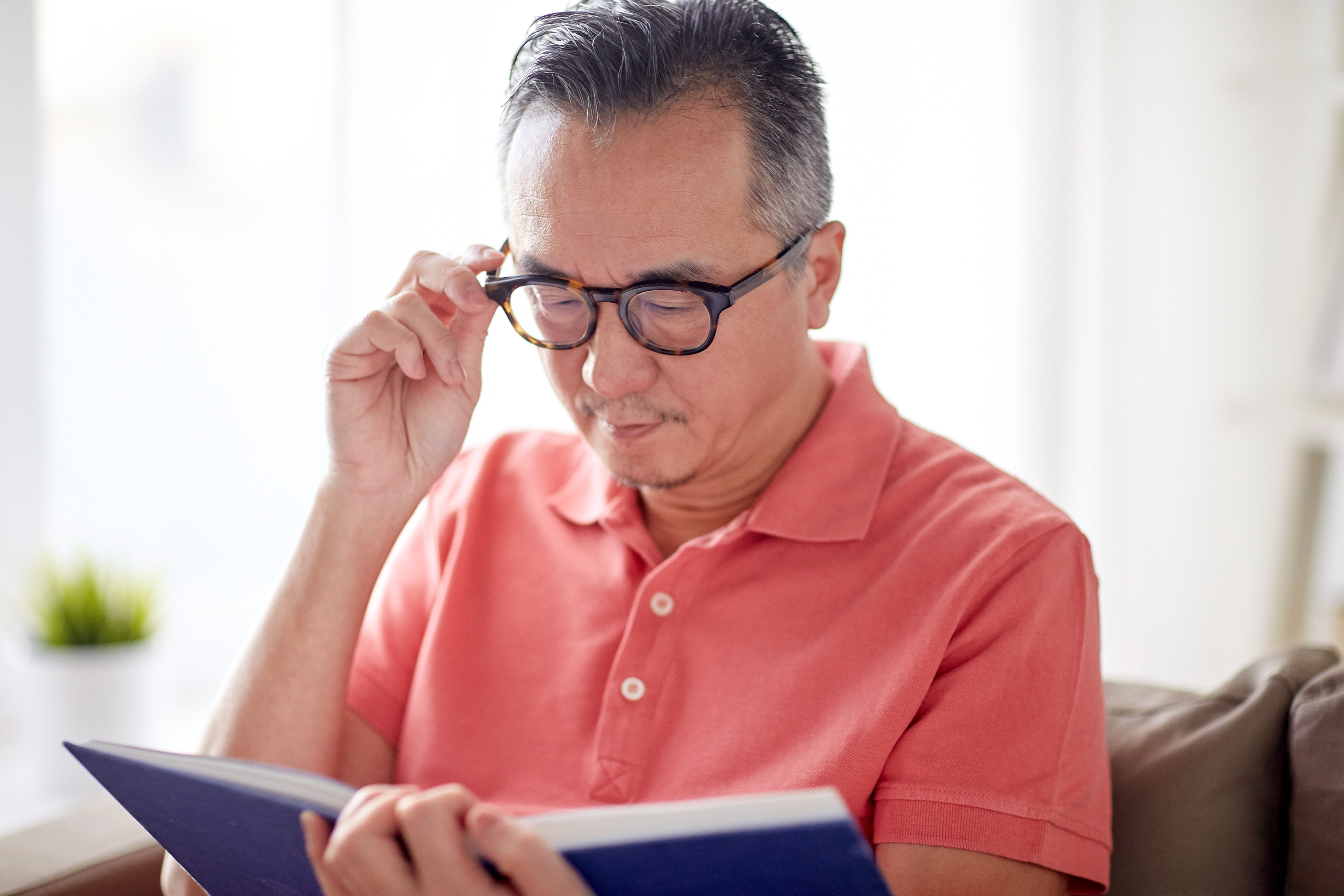 man-in-glasses-reading-book-at-home-PARV7F7
