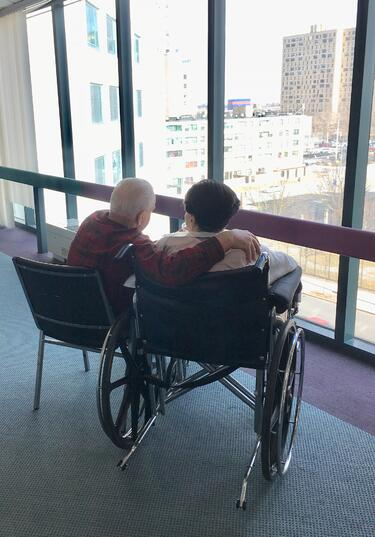 two-elder-people-in-wheelchairs-embracing-with-city-view