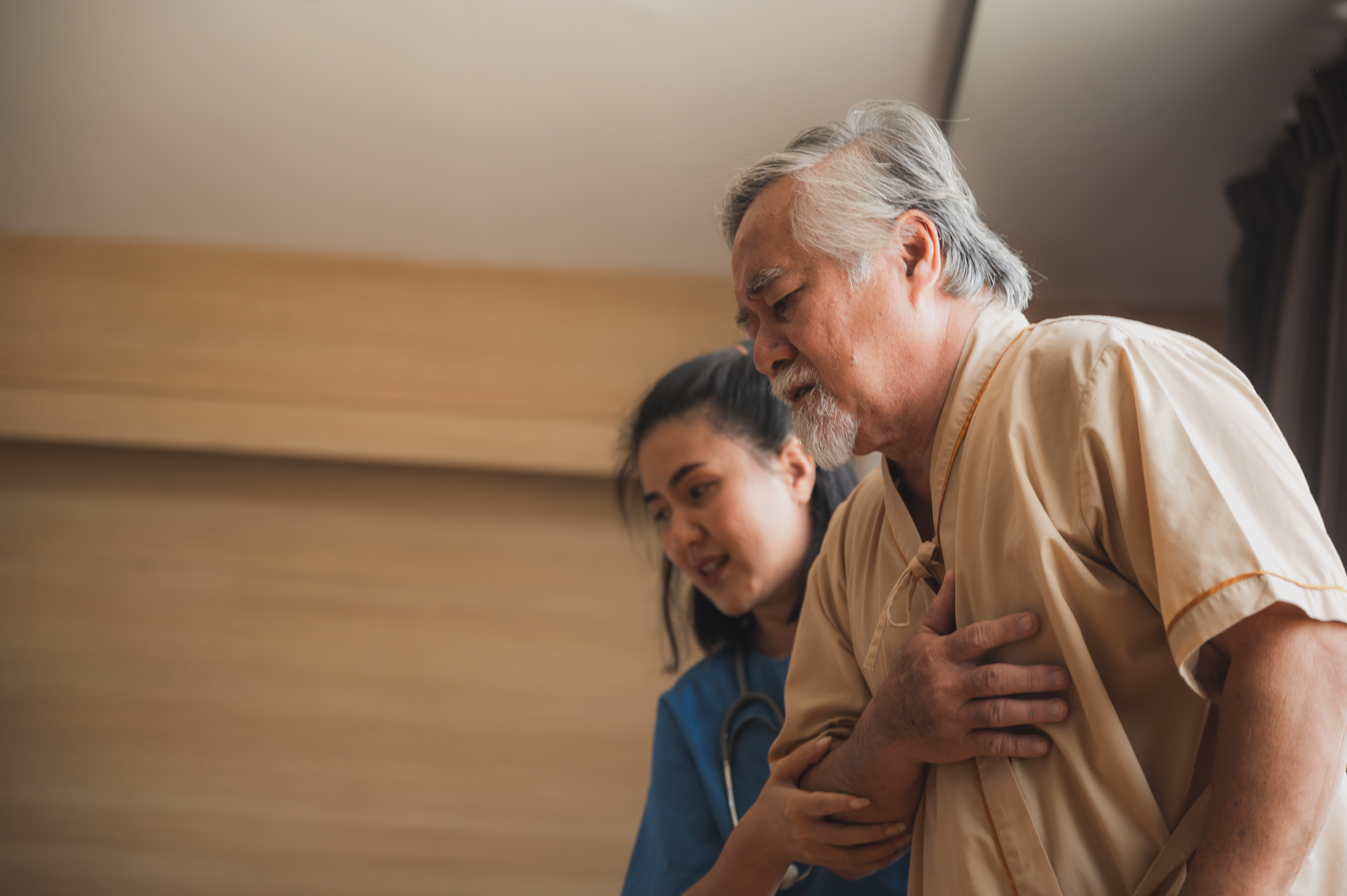 nurse-helping-older-man-walk-in-nursing-home
