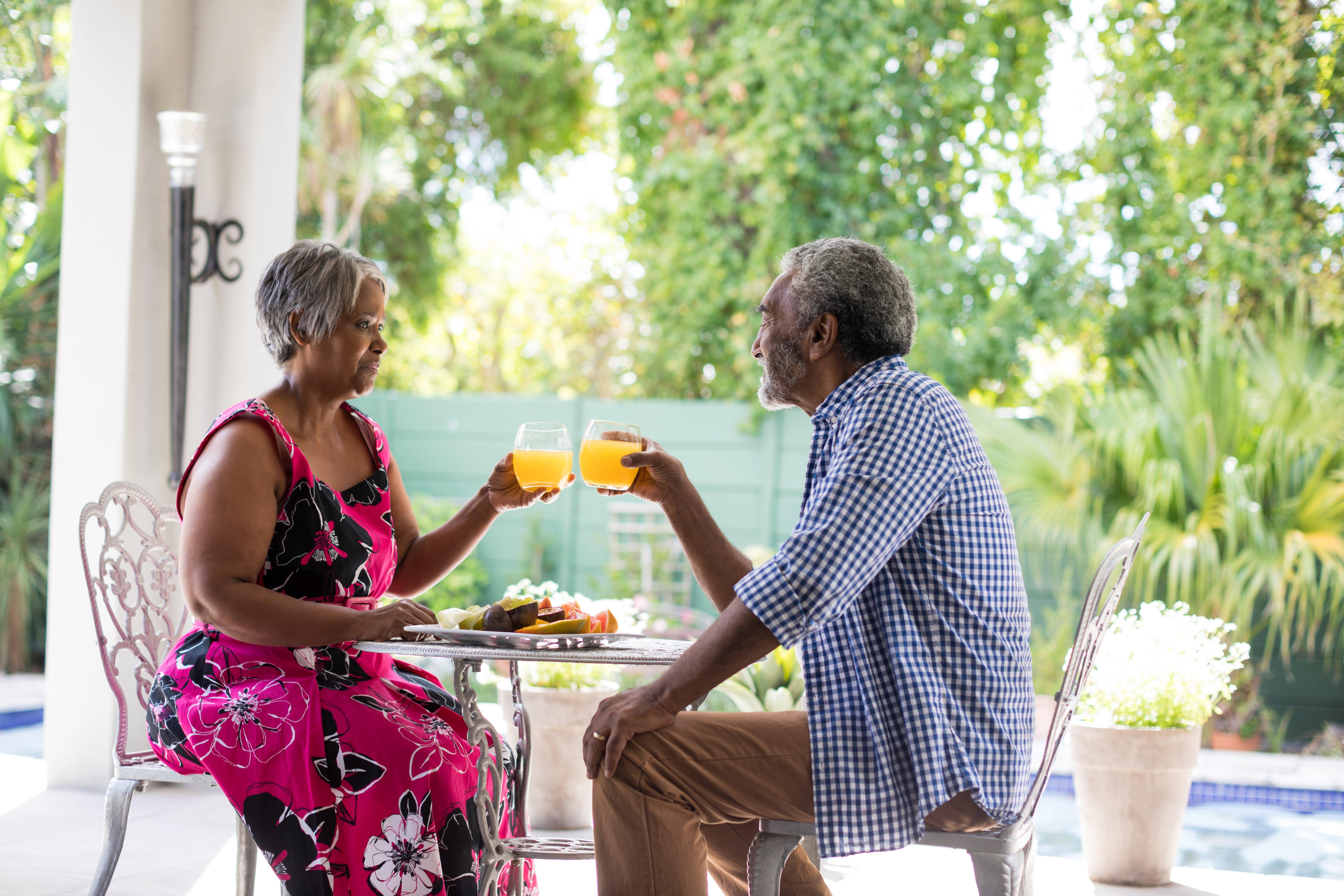 senior-couple-toasting-drinking-glasses-LTCQEK4