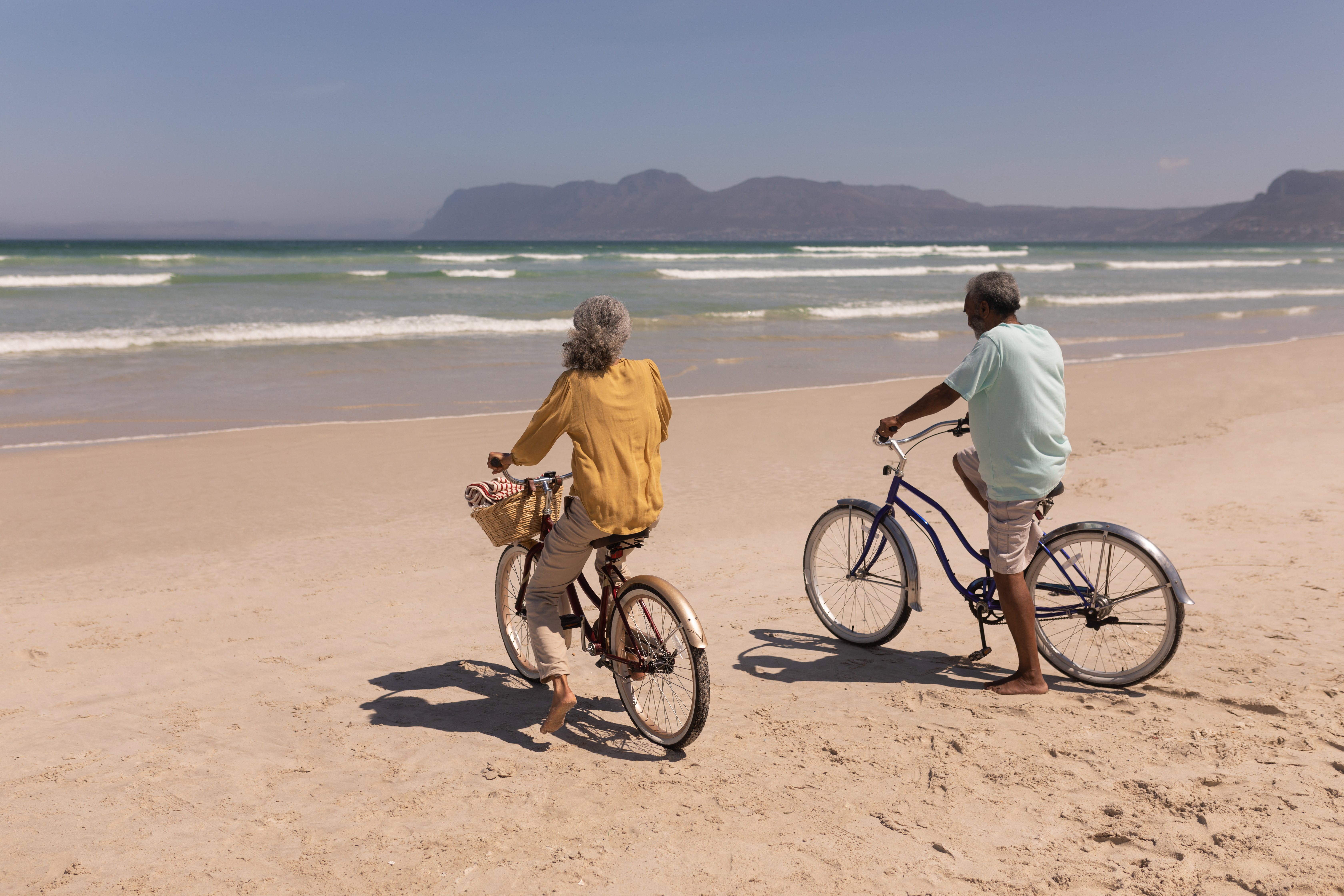 senior-couple-with-bicycle-standing-on-beach-in-th-HTSZQDA