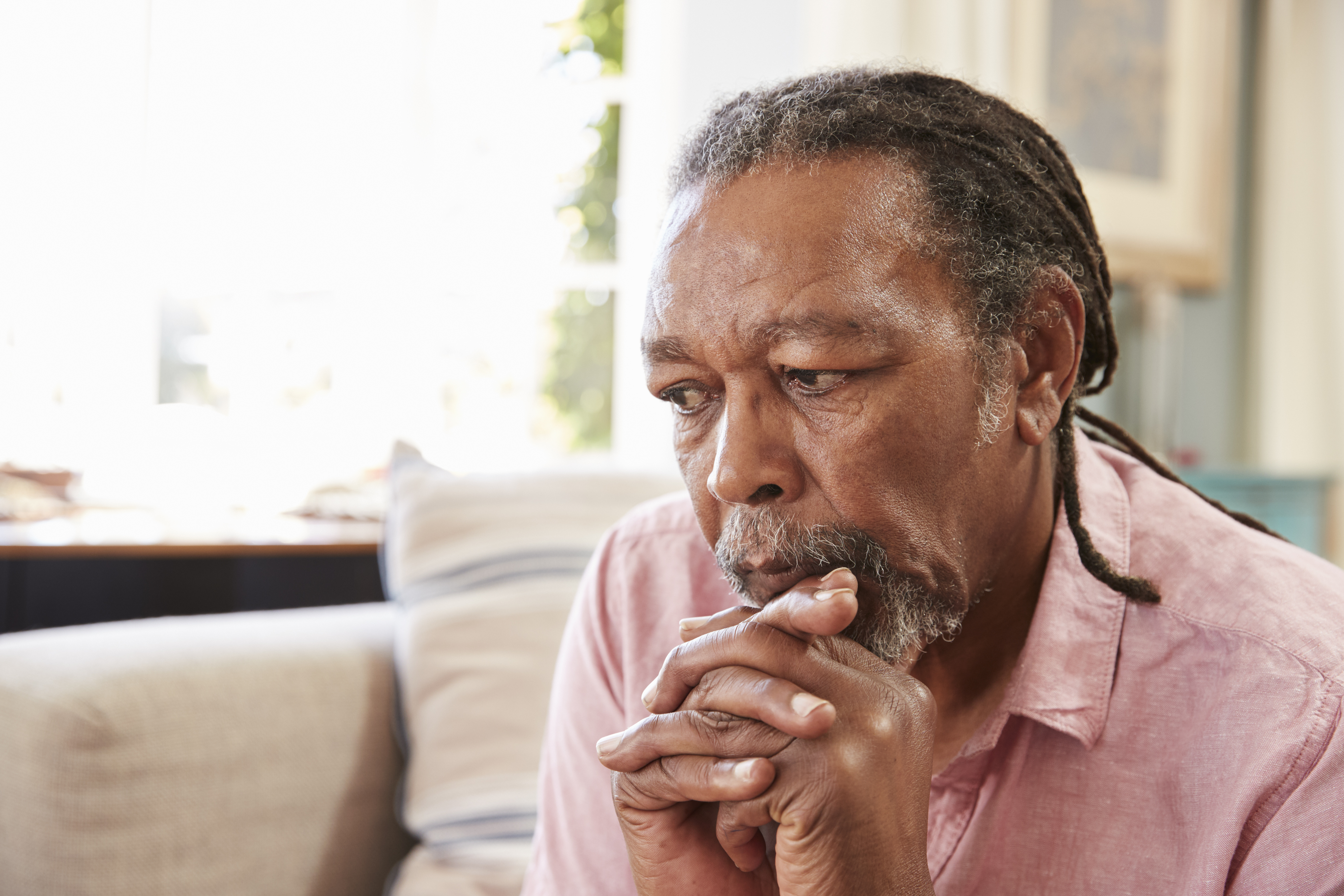 senior-man-sitting-on-sofa-at-home-suffering-from--PK6SFDJ