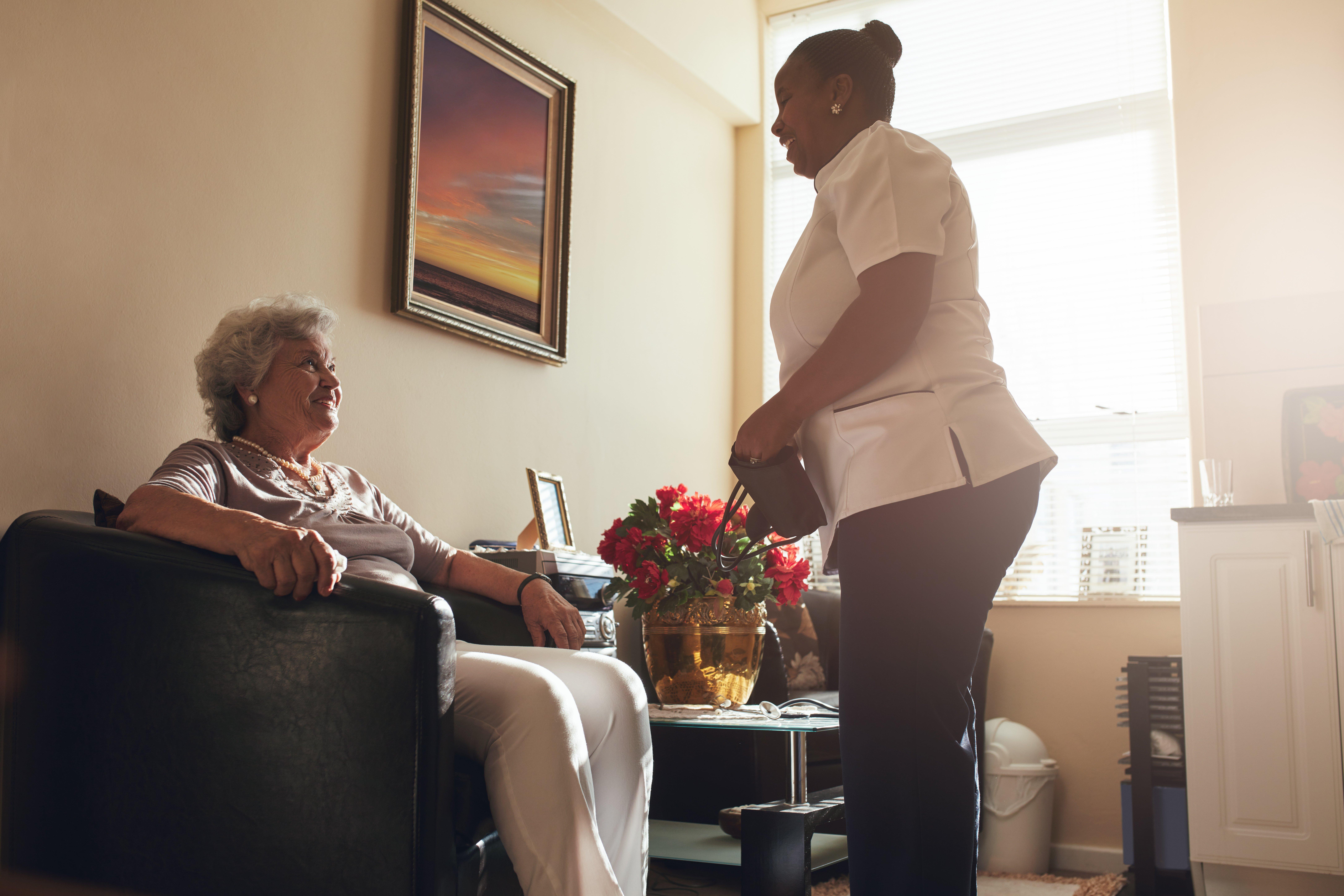 senior-woman-at-home-with-female-caregiver-PQP4YA9
