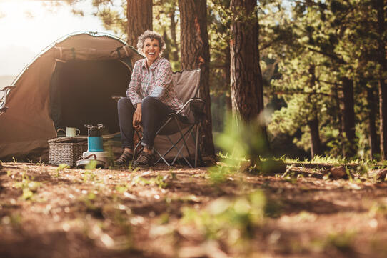 senior-woman-sitting-relaxed-outside-a-tent-P8XP6NQ