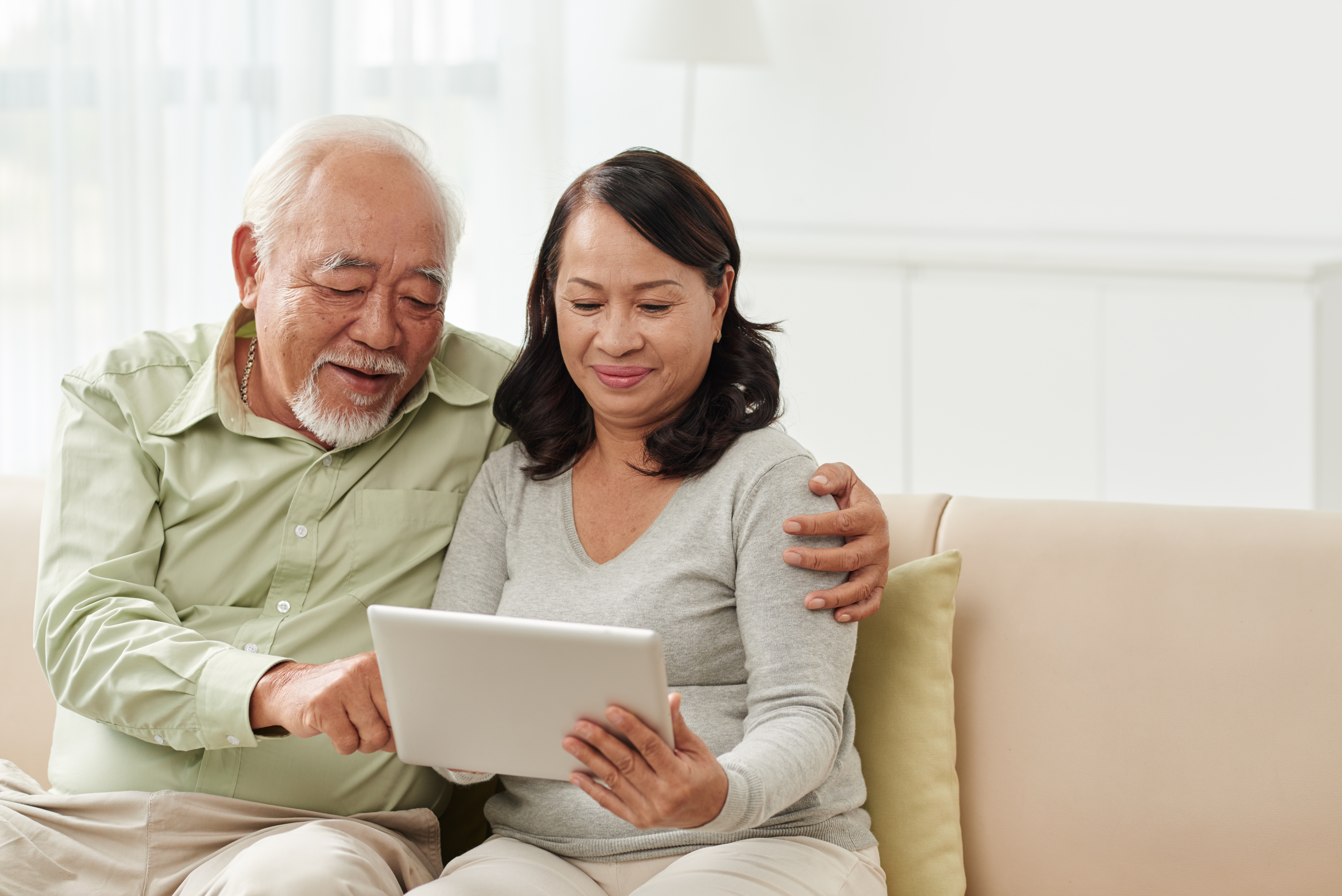 senior-couple-looking-at-tablet-on-couch