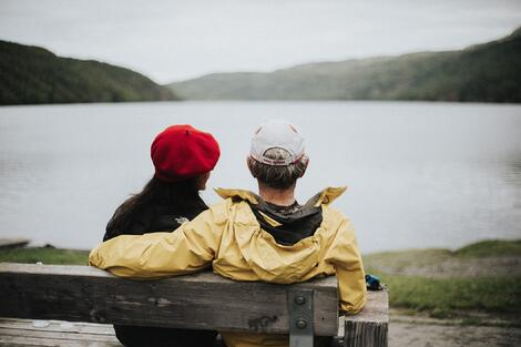 older-couple-sitting-side-by-side-by-lake