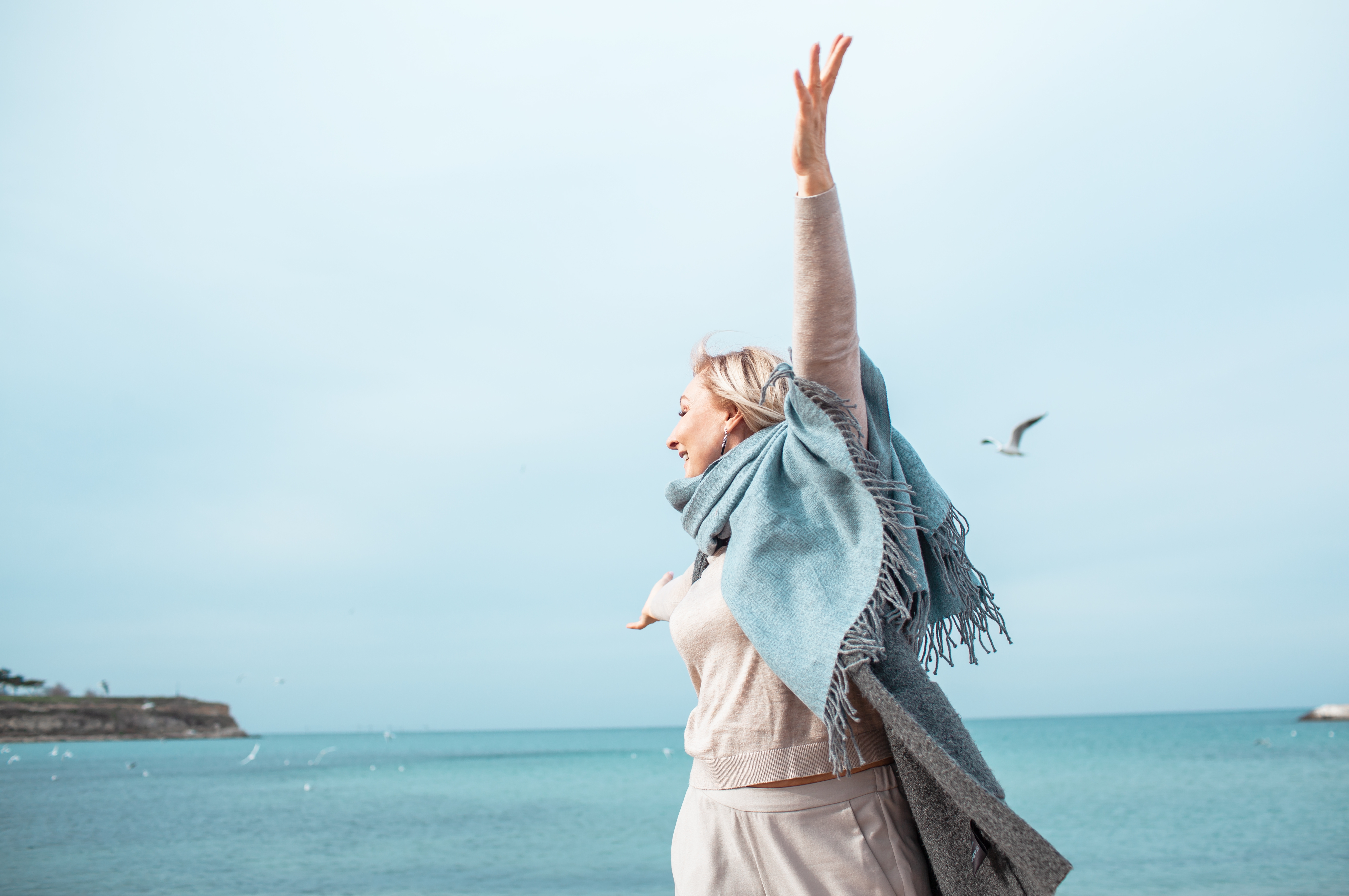 middle-aged-woman-skipping-by-the-sea-shore